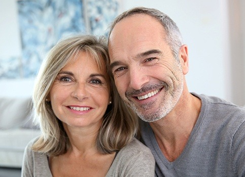 Smiling older man and woman after dental implant placement