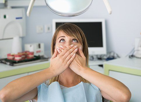 Woman at dental office for root canal covering her mouth