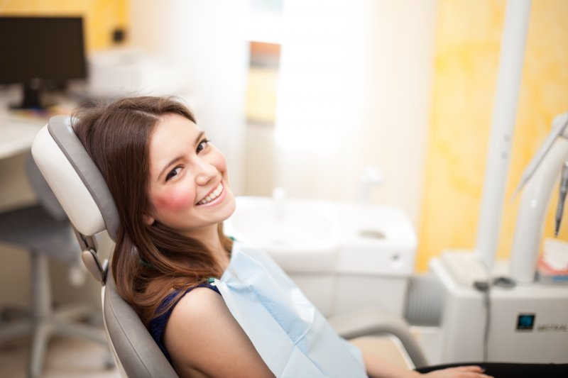 a young female sitting in the dentist's chair and smiling while waiting to see her dental professional