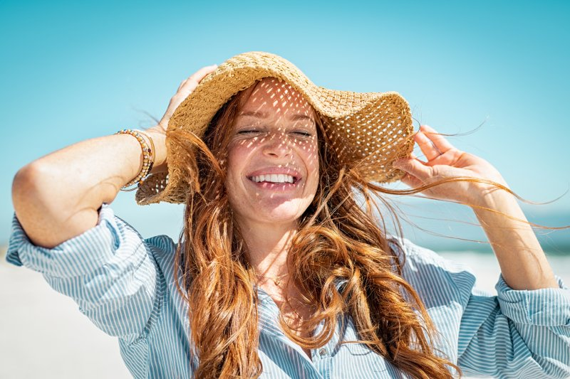 Woman in straw hat smiling by the ocean